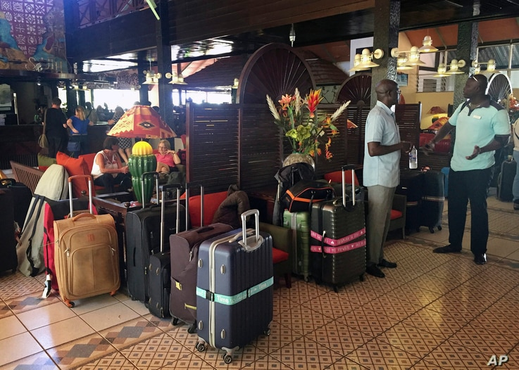 British and Dutch tourists wait in the lobby of their hotel to be taken to Banjul Airport, in Gambia, Jan. 18, 2017.