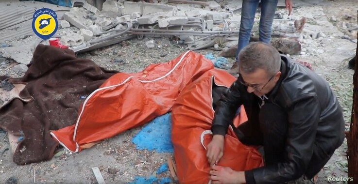 A man wraps a body in a street of rebel-held eastern Aleppo after artillery bombardment, which rescue workers say has killed at least 45 people, mostly women and children, Syria, in this still image taken on Nov. 30, 2016 from a social media website ...