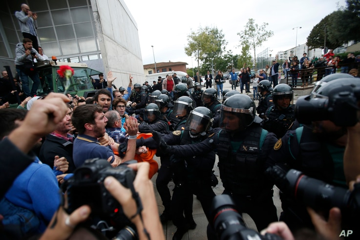 Civil guards clear people away from the entrance of a sports center, assigned to be a polling station by the Catalan government and where Catalan President Carles Puigdemont is expected to vote, in Sant Julia de Ramis, near Girona, Spain, Oct. 1, 201...