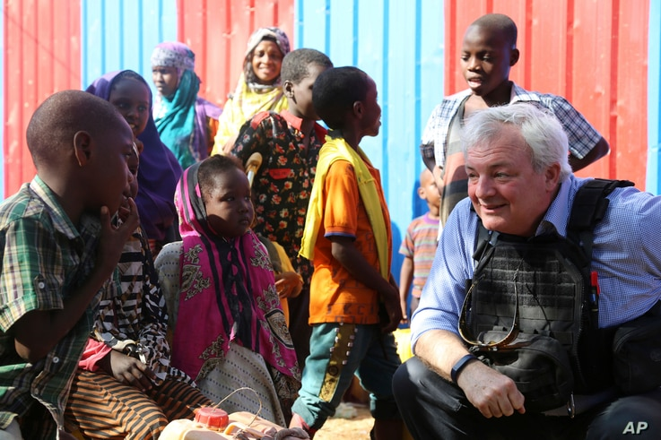 UN Humanitarian Chief Stephen O'Brien, right, meets with drought affected people during his visit to one of Mogadishu IDP camps in Somalia, March 6, 2017.