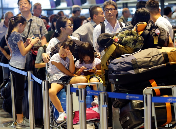 Passengers line up at check-in counter for Delta Air Lines at Narita international airport in Narita, east of Tokyo, Aug. 9, 2016.