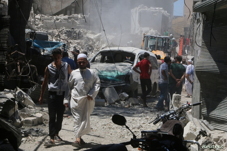 People inspect the damage at a site hit by a barrel bomb in the rebel held area of Old Aleppo, Syria, July 11, 2016.