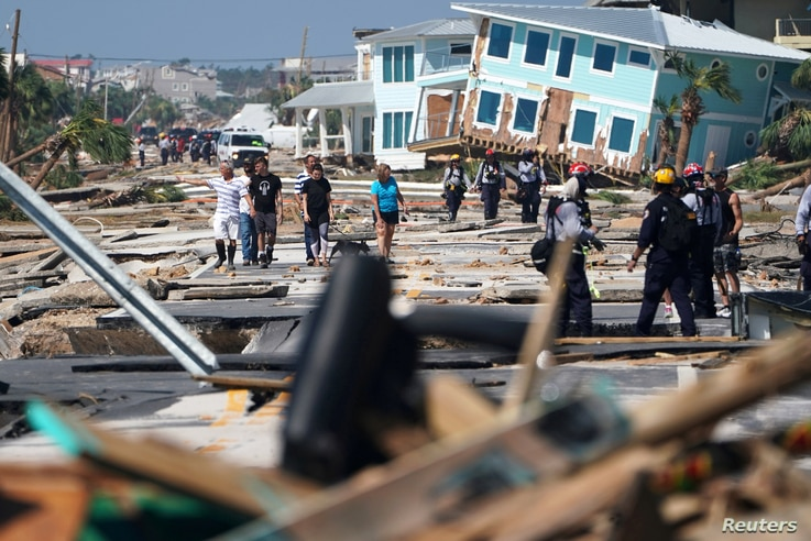 First responders and residents walk along a main street following Hurricane Michael in Mexico Beach, Florida, Oct. 11, 2018.