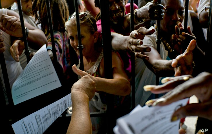 Santeria followers reach out for copies of the annual Letter of the Year, written by Afro-Cuban Santeria priests outlining predictions for the new year in Havana, Cuba, Jan. 3, 2017.