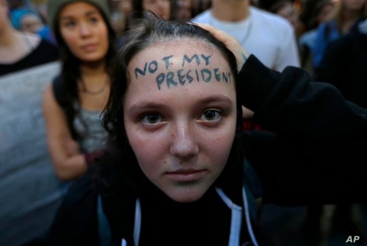 """Clair Sheehan has the words """"Not My President"""" written on her forehead as she takes part in a protest against the election of President-elect Donald Trump, Nov. 9, 2016, in downtown Seattle."""