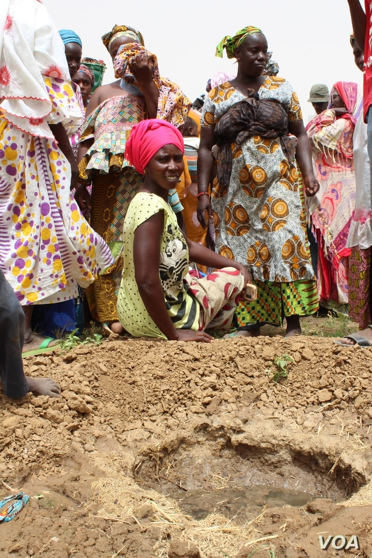 Women in Senegal's Woudourou village watch as workers from the Hadii Yahde project teach them to plant guava trees, May 17, 2017. (S. Christensen/VOA)
