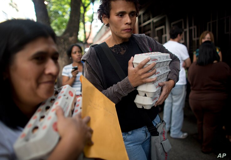 FILE - People carry boxes of eggs after buying them at government regulated prices in Caracas, Venezuela, during an egg shortage, Jan. 27, 2016. Venezuela's opposition-controlled parliament said Wednesday that inflation in the first seven months of 2...