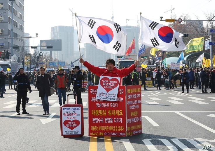 "A supporter of South Korean President Park Geun-hye holds the national flags during a rally opposing the parliamentary impeachment of Park in front of the National Assembly in Seoul, South Korea, Dec. 9, 2016. The signs read ""Oppose the impeachment...."