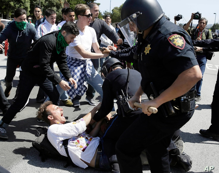 Police officers take a man into custody who was protesting against Republican presidential candidate Donald Trump outside the Hyatt Regency hotel during the California Republican Party 2016 Convention in Burlingame, Calif., April 29, 2016.