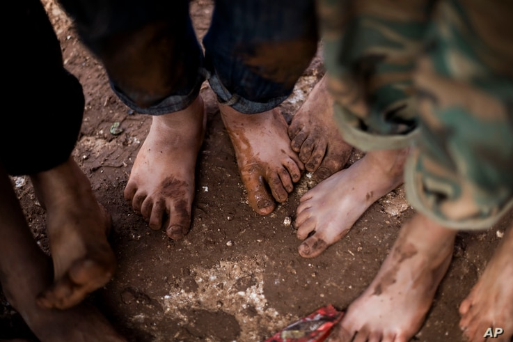 FILE - Displaced Syrian children gather barefoot in a refugee camp near Atma, Idlib province, Syria.