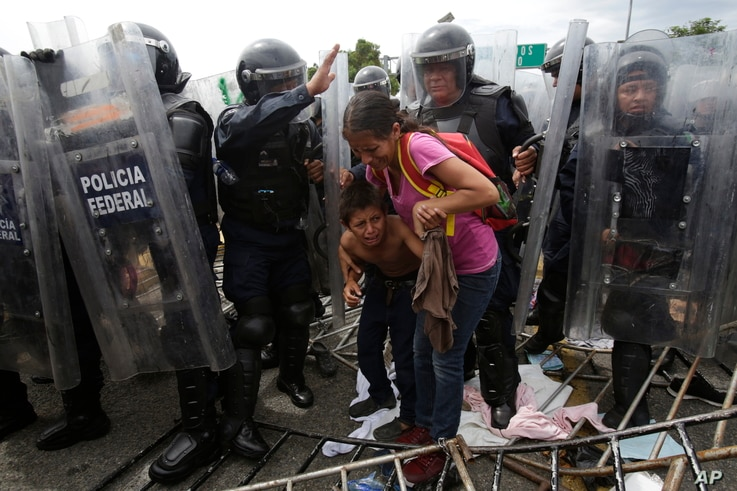 A Honduran migrant mother and child coweras they are surrounded by Mexican Federal Police in riot gear, at the border crossing in Ciudad Hidalgo, Mexico, Oct. 19, 2018.