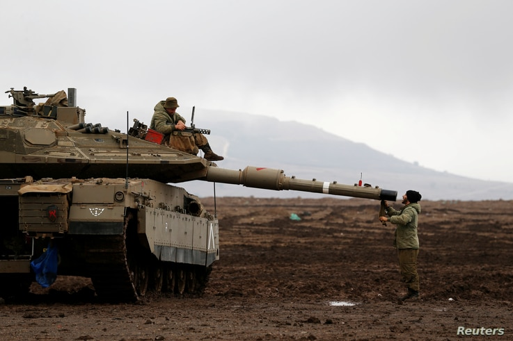 An Israeli soldier sits atop a tank and his comrade stands nearby in the Israeli-occupied Golan Heights, close to Israel's frontier with Syria, Nov. 22,  2017.