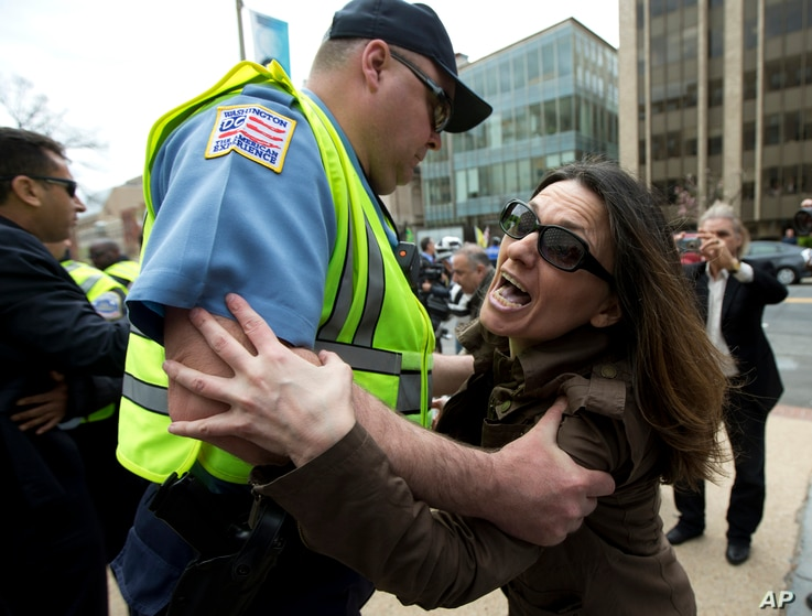 Anti-Erdogan protestor Deniz Lohja, an American of Turkish descent, is prevented by a Washington police officer from crossing near the supporters of Turkish President Recep Tayyip Erdogan, during a rally outside the Brookings Institution in Washingto...