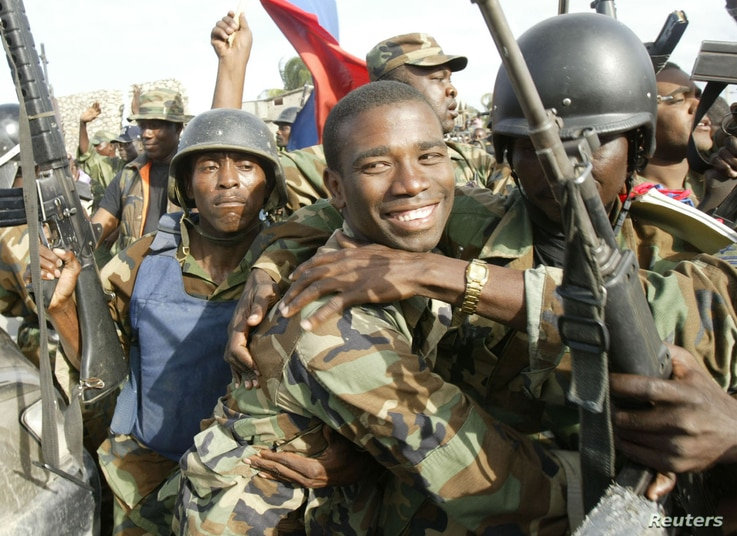 aitian National Revolutionary Liberation Front Commander-in-Chief, Guy Philippe, hugs other soldiers from the