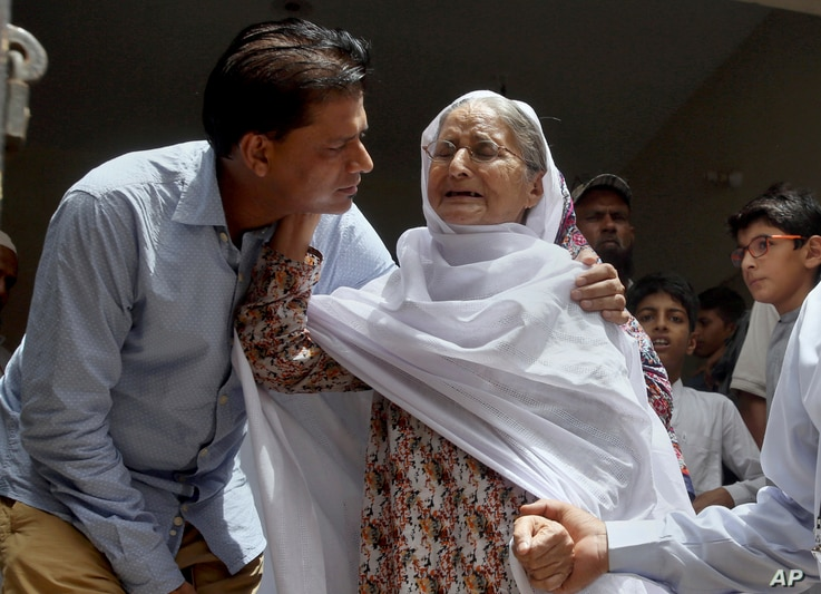 Abdul Aziz Sheikh, left, father of Sabika Sheikh, a victim of a shooting at a Texas high school, comforts an elderly woman at his home in Karachi, Pakistan, May 19, 2018.