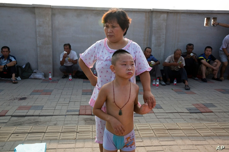 A woman and a child wait to return home near the site of an explosion in northeastern China's Tianjin municipality, Aug. 13, 2015.
