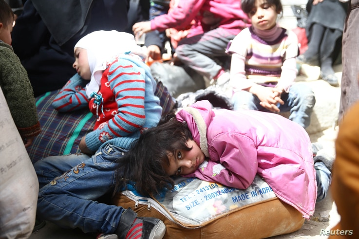 A girl looks at the camera during evacuations from the besieged town of Douma, Eastern Ghouta, in Damascus, Syria.