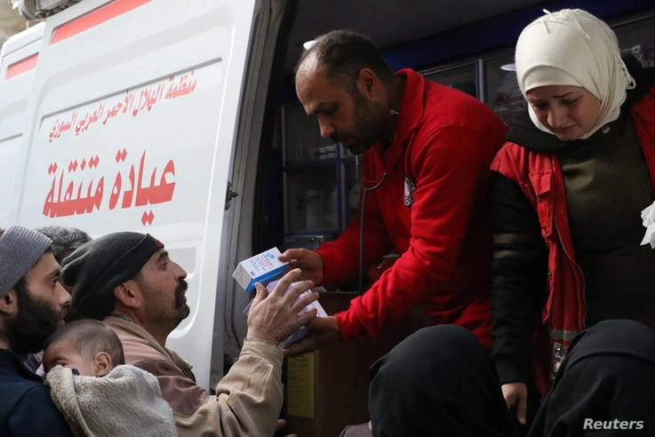 Syrian Red Crescent volunteers give medical supplies to civilians in Ghouta, Syria, March 5, 2018, in this picture obtained from social media.