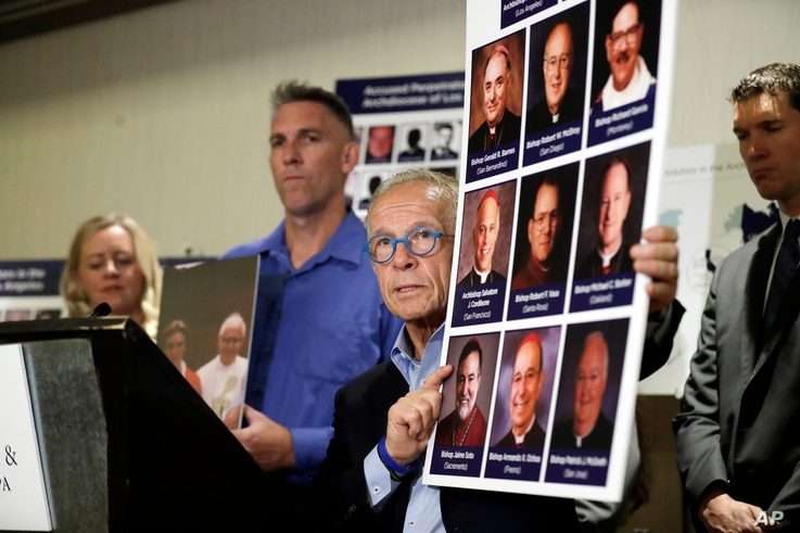 Attorney Jeff Anderson, center, holds photographs of clergy accused of sexual abuse, next to abuse survivor Tom Emens, second from left, Tuesday, Oct. 2, 2018, in Los Angeles.