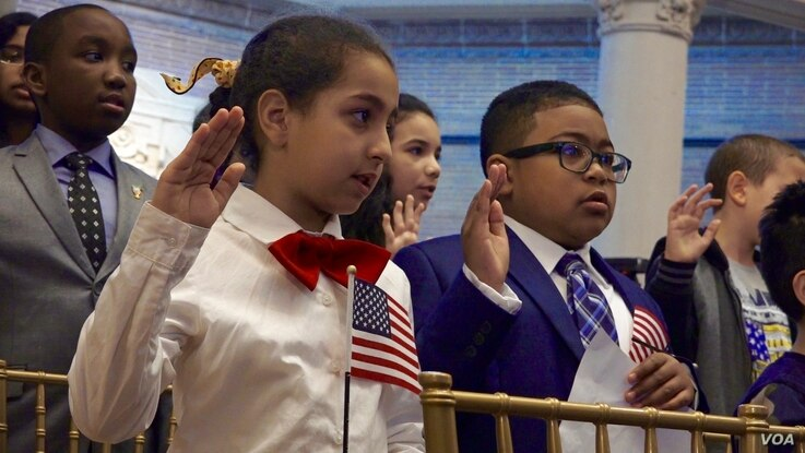 """Moroccan-American Sara, left, and Zambian-American Chonza Chingwe recite the """"Oath of Allegiance,"""" during a citizenship ceremony in New York, May 5, 2017. (R. Taylor/VOA)"""