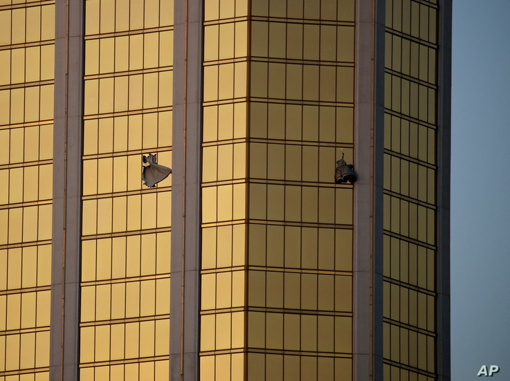 FILE - In this Oct. 2, 2017 file photo, drapes billow out of broken windows at the Mandalay Bay resort and casino on the Las Vegas Strip, following a mass shooting at a music festival in Las Vegas.