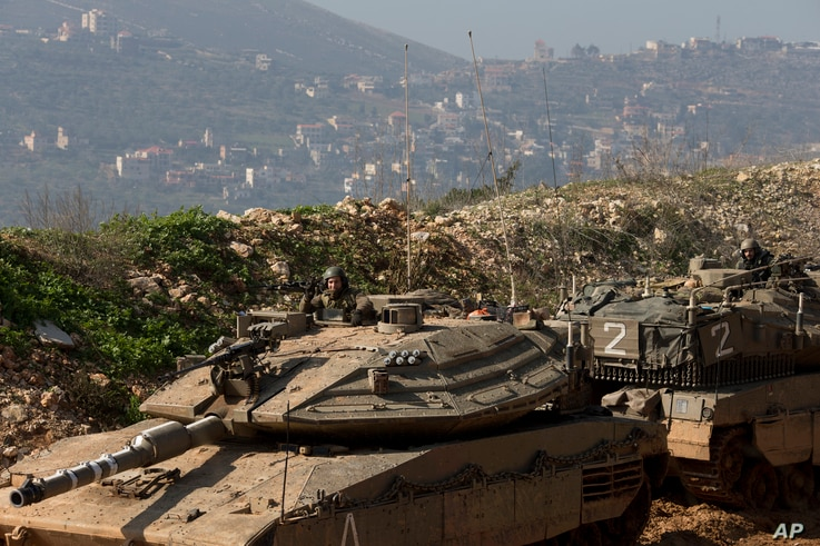 FILE - Israeli soldiers sit in tanks near the in Israel-Lebanon border, northern Israel, Jan. 20, 2015. Israel is on continuous alert for possible attacks from the Lebanon-based militant group Hezbollah.