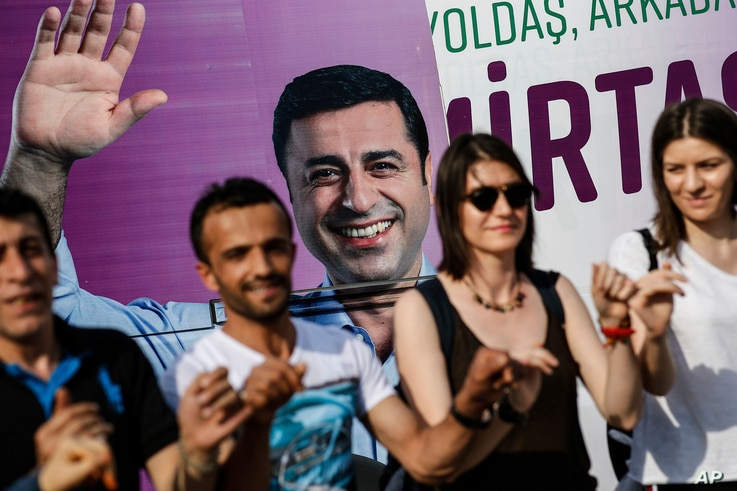 In this photo taken June 5, 2018, people dance in front of an election campaign poster of Selahattin Demirtas, Turkey's jailed pro-Kurdish politician and presidential candidate, in Istanbul.