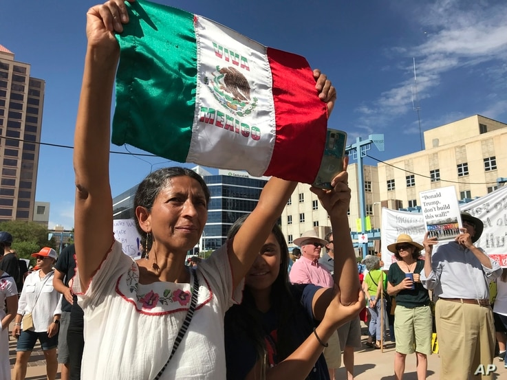 Margarita Perez of Albuquerque, with her daughter by her side, holds up a Mexican flag during a protest on Civic Plaza in Albuquerque, N.M., June 30, 2018. Perez was among thousands who gathered on the plaza to voice their opposition to U.S. immigrat...