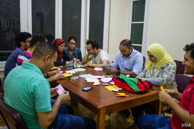 A group of volunteers, family members, and friends of political prisoners make origami gifts for the prisoners. (H. Elrasam/VOA)