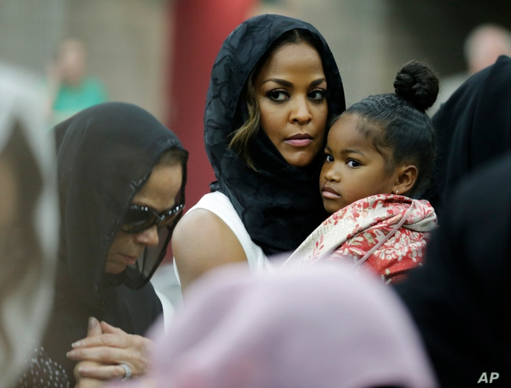 Muhammad Ali's wife, Lonnie, and her daughter Laila attend Muhammad Ali's Jenazah, a traditional Muslim service, at Freedom Hall in Louisville, Ky., June 9, 2016. Laila is holding her daughter, Sydney Jurldine Conway.
