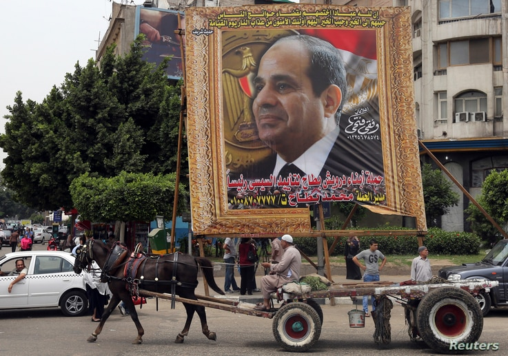 An Egyptian man on horse cart rides past a huge banner for Egypt's former army chief Field Marshal Abdel Fattah al-Sisi in downtown Cairo, May 6, 2014. Egyptian presidential frontrunner Abdel Fattah al-Sisi on Monday appeared to rule out reconciliati...