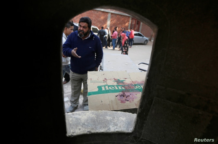 A man looks at bullet holes and blood stains at the site of attack on Mar Mina church in Helwan district on the outskirts of Cairo, Egypt, Dec. 29, 2017