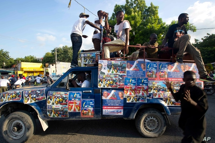 FILE -- A truck is covered with campaign signs in favor of Haiti's former President Jean-Bertrand Aristide and presidential candidate Maryse Narcisse. While it's easy to find Lavalas supporters in neighborhoods that were once Aristide strongholds, ...