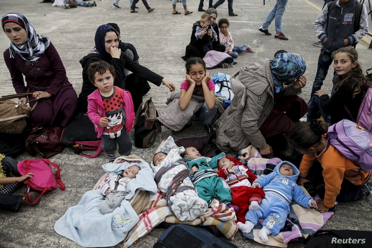 Five Syrian babies, three of them triplets (L to C), lie in blankets among their relatives as they arrive with other refugees and migrants aboard the passenger ferries Blue Star Patmos and Eleftherios Venizelos from the islands of Lesbos and Chios at...