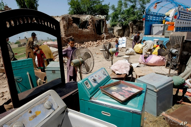 FILE - Afghan refugees who fled their country due to war, collect their belongings after Pakistani authorities demolished their home in suburbs of Peshawar, May 1, 2015.