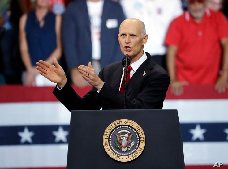 Florida Gov. Rick Scott gestures as he appears with President Donald Trump during a rally, Oct. 31, 2018, in Estero, Fla. Scott is running for U.S. Senate against Democrat Bill Nelson.