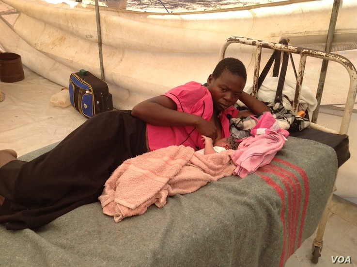 A mother lies with her child in a makeshift clinic after delivering the baby at the Chingwizi transit camp, February 2016. (S. Mohfu/VOA)
