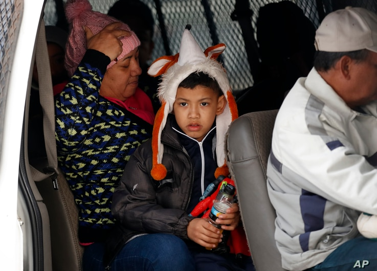 FILE - A migrant family waits with others before being transported by Mexican authorities to the San Ysidro port of entry to begin the process of applying for asylum in the United States in Tijuana, Mexico, Jan. 29, 2019.