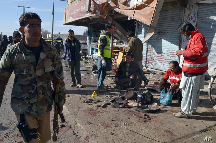 Pakistani police officers and rescue workers gather at the site of suicide bombing in Quetta, Pakistan, Wednesday, Jan. 13, 2016.