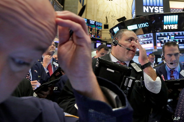 FILE - Anthony Riccio, center, works with fellow traders on the floor of the New York Stock Exchange, Nov. 9, 2016. Investors have been yanking money out of bonds around the world, sending prices tumbling and wiping out several months of gains in wid...