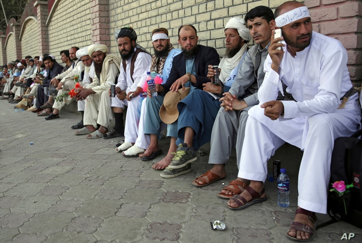 FILE - Members of the Helmand Peace Convoy, who trekked across the country on foot calling for an end to the war, arrive in Kabul, Afghanistan, June 18, 2018.