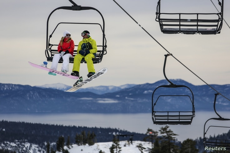 FILE - Snowboarders ride a lift with Lake Tahoe in the background at Squaw Valley in Olympic Valley, California, Dec. 5, 2015.