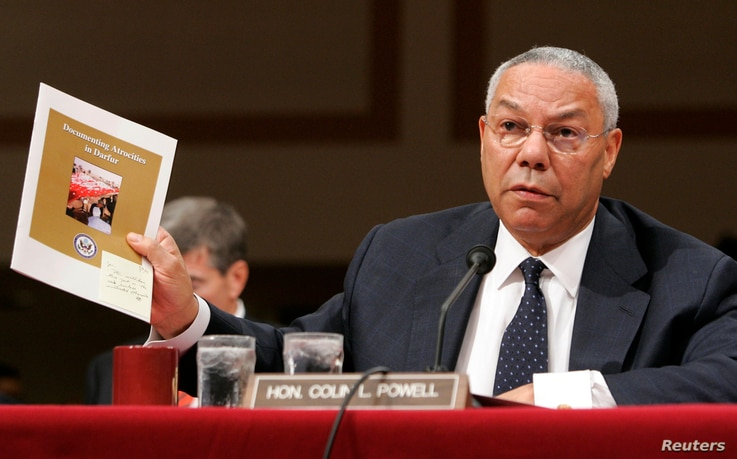 U.S. Secretary of State Colin Powell holds up a State Department report documenting atrocities in Darfur while testifying before the Senate Foreign Relations Committee on Capitol Hill in Washington September 9, 2004. Powell said that genocide has occ