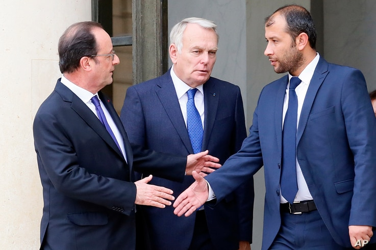 FILE - Then-French President Francois Hollande, left, flanked by his foreign minister, Jean Marc Ayrault, center, shakes hands with Rahed Saleh, director of Syrian Civil Defense White Helmets, after their meeting with a Syria delegation at the Elysee...
