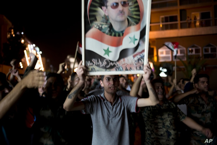 Syrian soldiers celebrate Bashar Assad's presidential re-election, in Damascus, Syria, June 4, 2014.