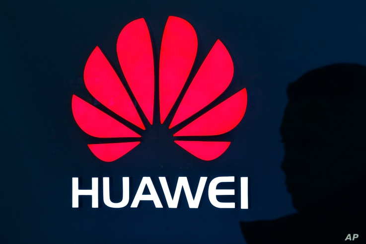 A man is silhouetted as he walks by a Huawei retail store at a shopping mall in Beijing, China, Dec. 11, 2018.