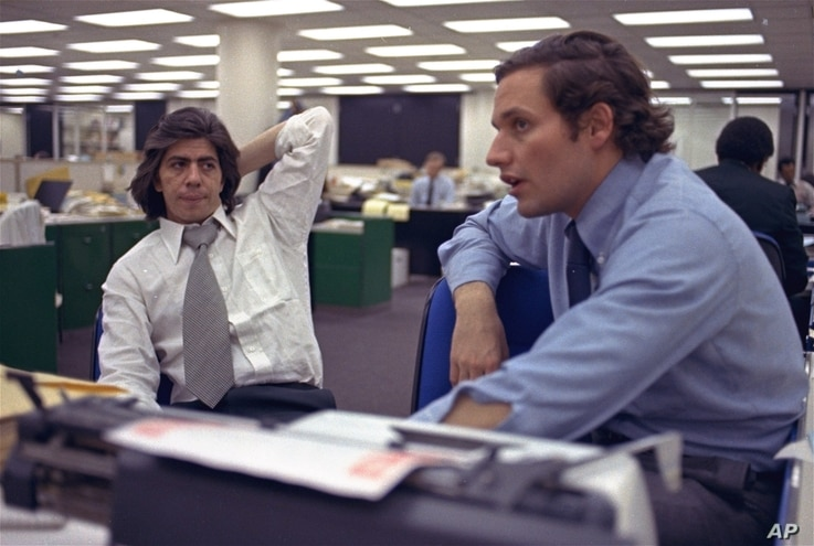 FILE - Reporters Bob Woodward, right, and Carl Bernstein, whose reporting of the Watergate case won them a Pulitzer Prize, sit in the newsroom of The Washington Post in Washington, May 7, 1973.