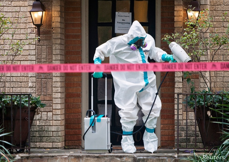 A member aA member of the CG Environmental HazMat team disinfects the entrance to the residence of a health worker at the Texas Health Presbyterian Hospital who has contracted Ebola in Dallas, Texas, Oct.12, 2014.of the CG Environmental HazMat team d...
