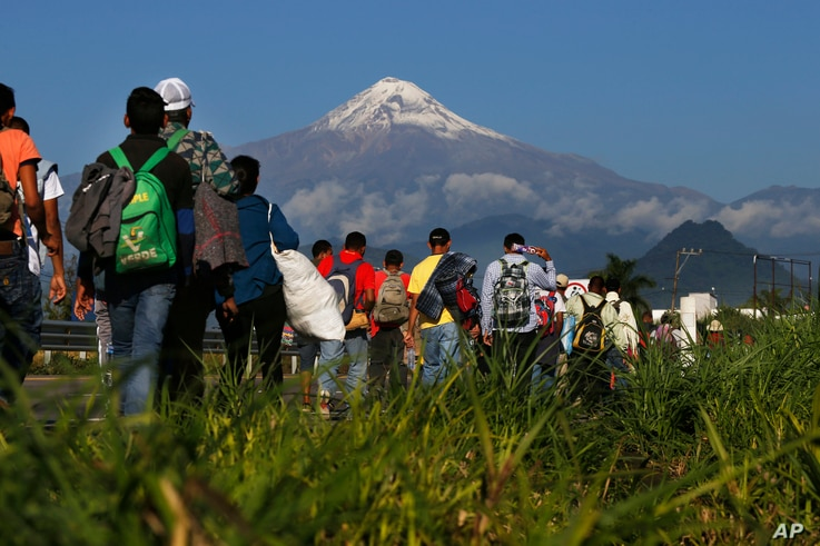 Central American migrants begin their morning trek as part of a thousands-strong caravan hoping to reach the U.S. border, as they face the Pico de Orizaba volcano upon departure from Cordoba, Mexico, Monday, Nov. 5, 2018.