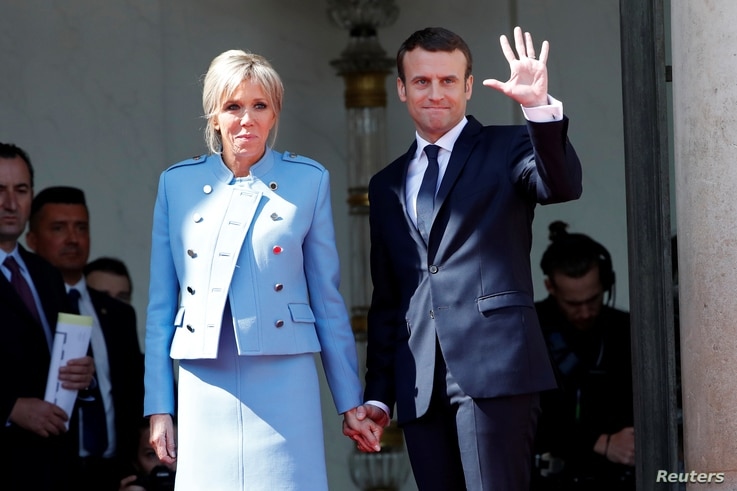 French President Emmanuel Macron and his wife, Brigitte Trogneux, wave to former President Francois Hollande as he leaves after the handover ceremony at the Elysee Palace in Paris, May 14, 2017.